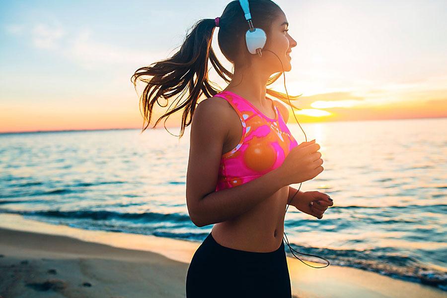 chica corriendo por la playa escuchando musica
