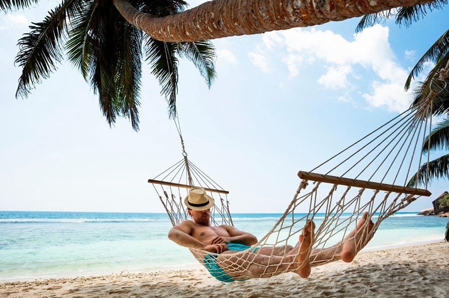 hombre con hamaca en la playa